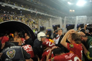 Turkish policemen protect Galatasaray's players after their victory over Fenerbahce at the end of their  match at Sukru Saracoglu Stadium in Istanbul in May 2012.