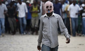 A masked protester walks during a protest against President Pierre Nkurunziza's decision to run for a third term