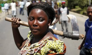 A female protester holds an axe during a protest against Nkurunziza.