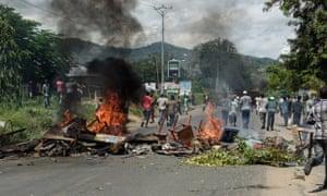 Protesters run near a barricade in Bujumbura in Wednesday.