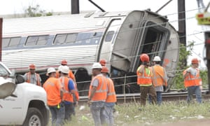 Workers look at one of the carriages of the derailed Amtrak train, which crashed just outside Philadelphia.