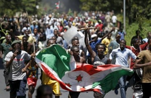 Some protesters carry the Burundian flag, whilst others hold axes and sticks.