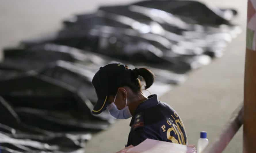 A police officer in front of bodies under shrounds.