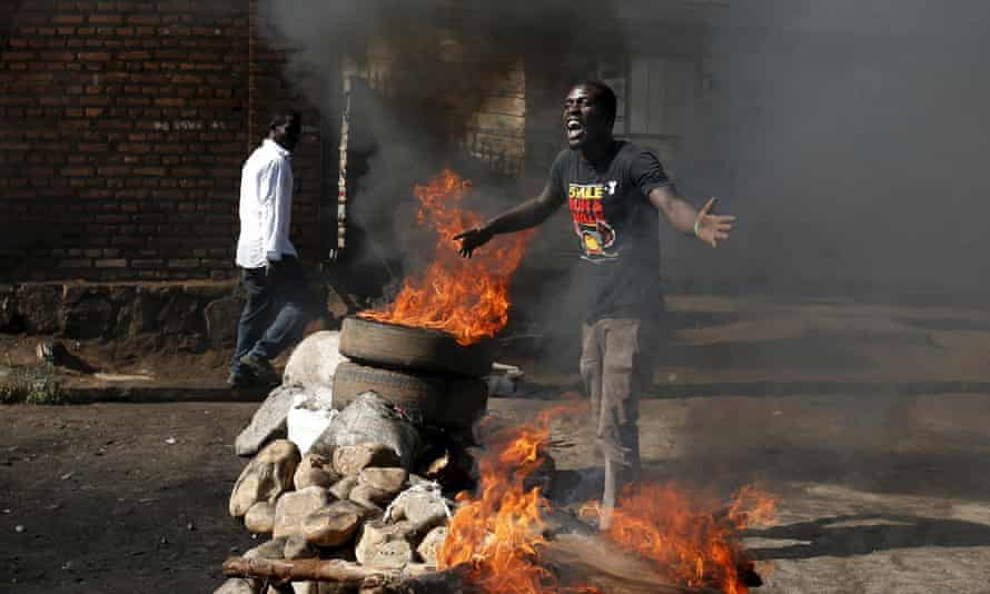 A anti-Nkurunziza's protester gestures in front of a burning barricade in Bujumbura.