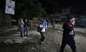 People who were trapped inside walk out of the guest house after being rescued by the security forces in Kabul.