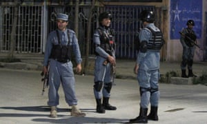 Afghan policemen stand guard near the hotel after the attack by Taliban militants.