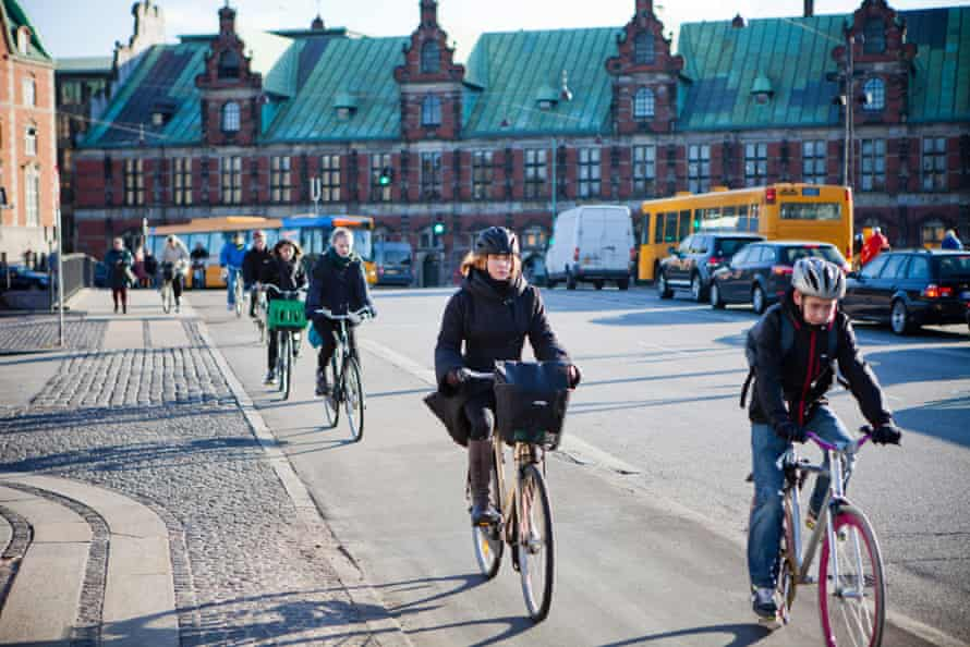 Cyclists use a cycle lane to travel past the Copenhagen Stock Exchange, center, in Copenhagen, Denmark