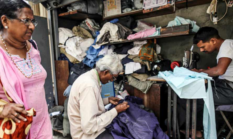 A woman walks past roadside tailors working at a stall in Mumbai, India.