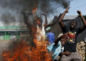 Protesters gesture in front of a burning barricade in Bujumbura. The head of Burundi's army said that an attempted coup had failed and forces loyal to Nkurunziza were in control