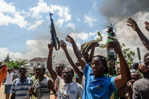 A man holds a gun taken from a police officer as another holds a molotov cocktail after heavy clashes with police in the Musaga neighbourhood