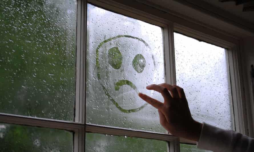 Sad face drawn on a window