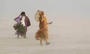 Women use their veils to protect themselves from sand as they walk along the banks of the river Ganges during a dust storm in Allahabad, India.