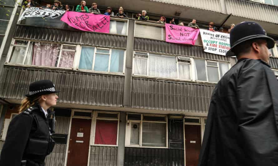 Police walk past as activists from Housing Action Southwark and Lambeth resist a family's eviction from a flat in an estate that had been marked for demolition.