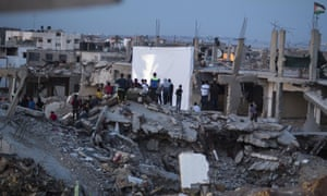 A world away from Cannes film festival, in the el-Shuja'ia neighbourhood, east of Gaza City, Palestinians watch a film projected on to a destroyed house during the Karama-Gaza Human Rights film festival, which has been dubbed 'Red Carpet'.
