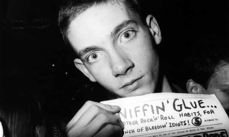 A punk holding up a copy of Sniffin' Glue.