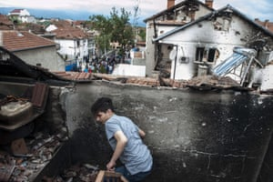 Tensions between the Slavic-speaking majority of Macedonia and ethnic Albanians have been heightened after a police raid in the northern town of Kumanovo resulted in the deaths of 14 ethnic Albanians and eight policemen. Here a boy walks through the rubble of a damaged house in the town