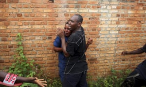 In Bujumbura, Burundi, a man tries to protect a female police officer accused of shooting a protester opposed to the president's decision to run for a third term. A mob of protesters chased, caught, beat and stoned the woman, who was later released back to the police.