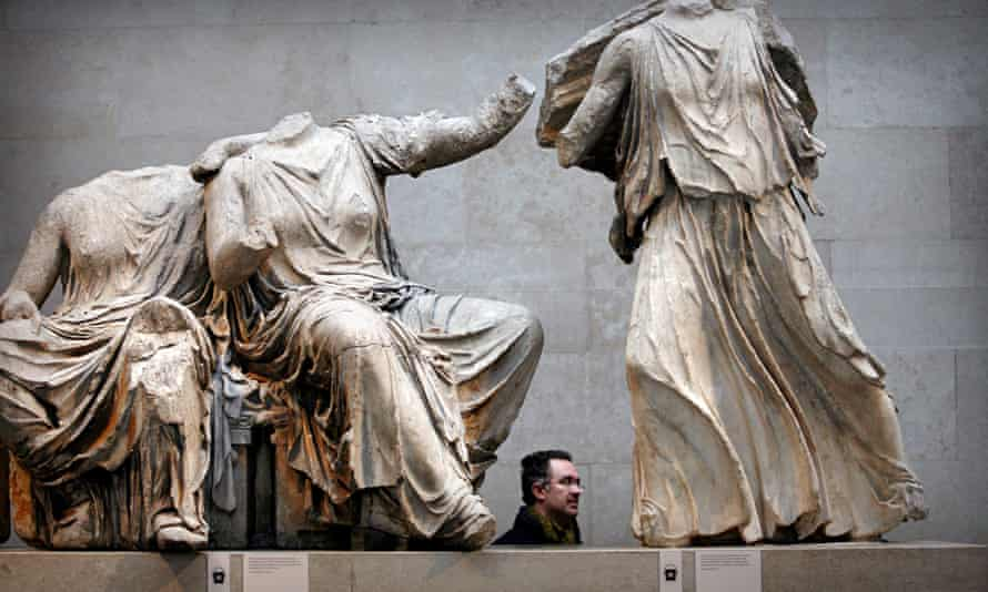 A visitor passes part of the Elgin Marbles collection at the