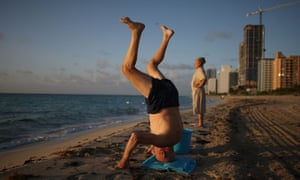 MIAMI BEACH, FL - JULY 25:  Michael Landman (L) and Monique Landman do their morning exercise as the sun rises over the beach July 25, 2007 in Miami Beach, Florida. They say they have been visiting the beach early in the morning for the last 40 years.  The long stretch of beach sees walkers and early-morning exercisers along with other activity.  (Photo by Joe Raedle/Getty Images)75620861beachearlyEOS1DMkIII-0000514720morningoceanrise elderly old people headstandsunswimtouristvisitwater