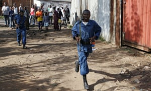 Men in police uniforms walk along a street in Bujumbura, Burundi, on Friday