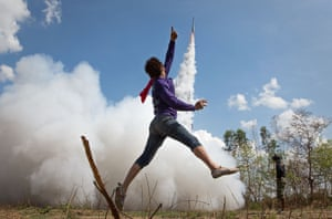 "A young man jumps in the air and cheers as his home-made rocket takes off at the Bun Bang Fai rocket festival in Yasothon, Thailand. The festival celebrates Buddha and the beginning of the rainy season. <br>You can see more of Taylor Weidman's images from the festival <a href=""http://www.theguardian.com/news/gallery/2015/may/14/thailands-homemade-rocket-festival-in-pictures-bun-bang-fai"">here</a>"