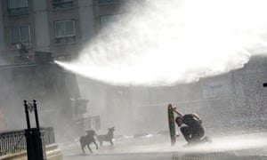 A protester takes cover from a water cannon behind his skateboard during a demonstration to demand changes in the education system in Santiago, Chile.