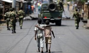 Boys walk behind patrolling soldiers in Bujumbura on Friday