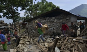 An elderly woman is carried by her son on a basket past the remnants of a house that collapsed during the latest earthquake in north-eastern Nepal