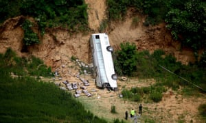 A bus lies at the bottom of a ravine after overturning and falling in to a valley in Chunhua county, Shaanxi province, China. At least 35 people were killed in the accident.