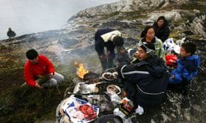 An Inuit fisherman and his family have a seal meat barbecue in Greenland.