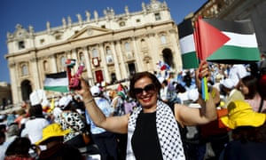 A member of the crowd waves Palestinian flags in Saint Peter's square on Sunday.