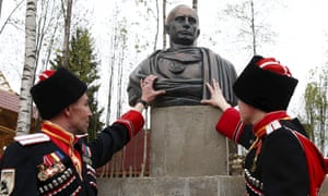Cossacks stand next to a bust of Russian President Vladimir Putin which depicts him as a Roman emperor
