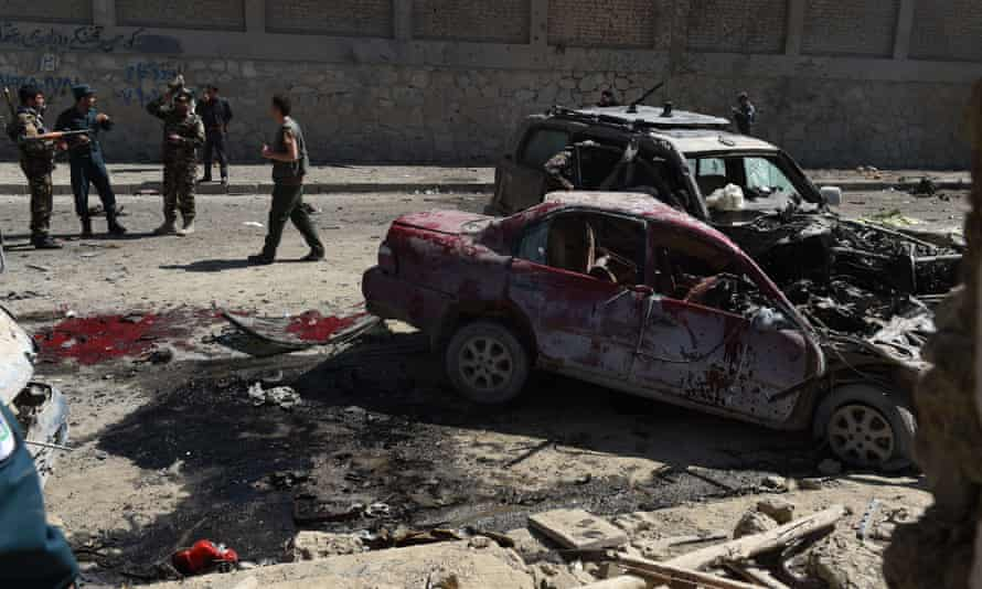 Afghan and foreign security forces inspect the site of the suicide attack near Kabul airport.