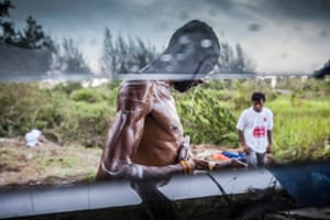 Following his rescue, a man washes at the Kuala Langsa camp. Up to 8,000 people are believed to be stuck on vessels on the Thai, Indonesian and Malaysian coasts.