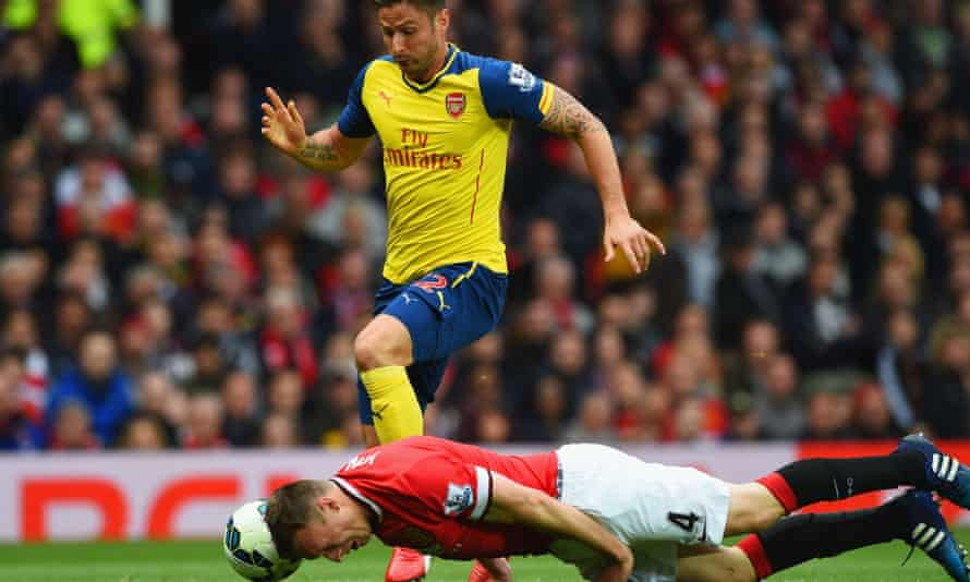 Phil Jones of Manchester United attempts to head the ball away from Arsenal's Olivier Giroud.