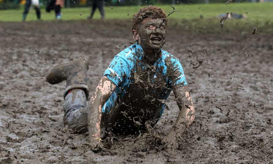 Tom Wilder, 17 from Kent, dives in the mud at the Glastonbury Festival on 23 June 2011