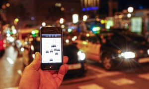 A man holds an iPhone displaying the Uber app in front of a queue of traffic.