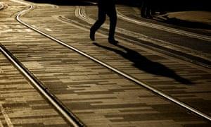 Silhouette of a man walking between tram tracks.