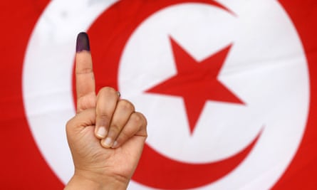 A Tunisian woman raises her ink-stained finger after casting her vote in the country's first post-revolution presidential election on 23 November 2014.