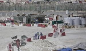 Photograph taken during a government organised media tour of foreign workers walking between safety barricades at the site of the pitch of the al-Wakra stadium under construction in Doha