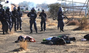 Police officers with the bodies of dead strikers after the shootings.