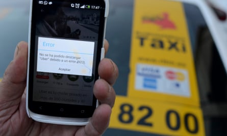 Alcobendas, Spain. 9th December 2014 - A taxi driver holds his mobile phone screen showing an error as he tries to download the 'Uber' application to his smartphone after a judge ordered US-based ride-sharing and taxi service Uber to cease all activities in Spain.