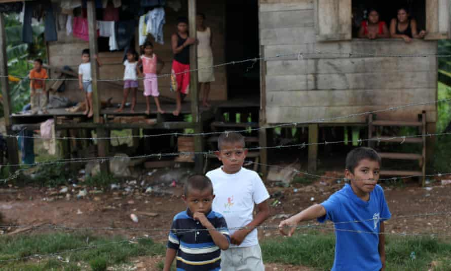 Residents stand outside their home as they watch soldiers unload supplies from a military helicopter for people who suffered damage from Tropical Storm Ida in Bluefields, Nicaragua