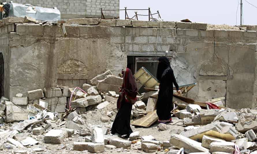 Yemeni women walk amid rubble of houses