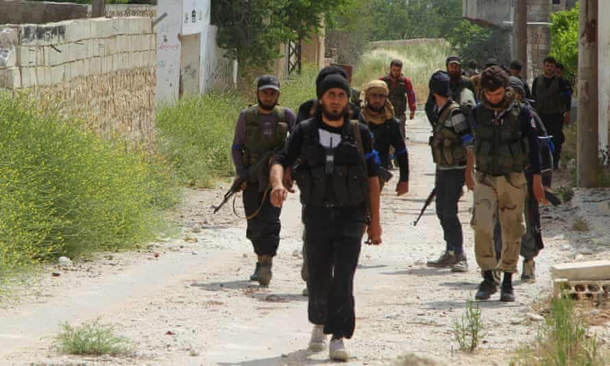 Rebel fighters walk in Mastouma village, Idlib, after they said they had advanced on the area.