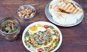 Olives, pistachios and hummus with chickpeas, chilli and pine nuts on a wooden platter.
