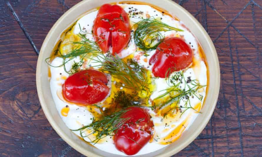 Crème fraîche 'spun through with salty, fiery harissa paste' in a bowl on a platter