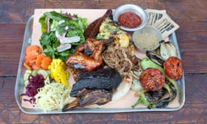 Berber & Q's metal platter of chicken wings, chicken thighs, short rib, merguez sausages, dill pickles and mixed pickles