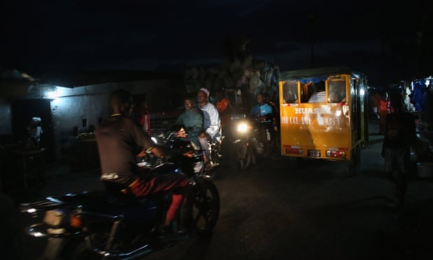 People drive through the dark in the favella of West Point, where few homes have electricity in Monrovia, Liberia.