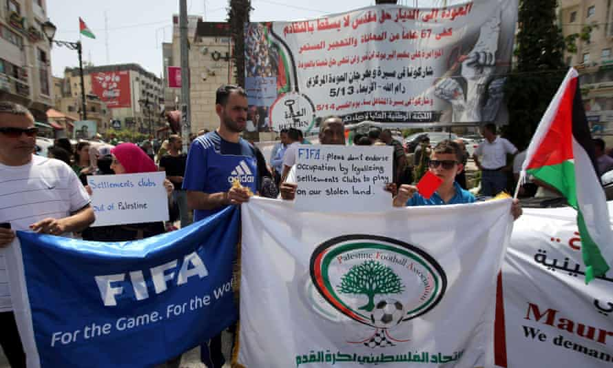 Palestinians hold banners as they demonstrate in Ramallah, demanding the expulsion of Israel from Fifa.